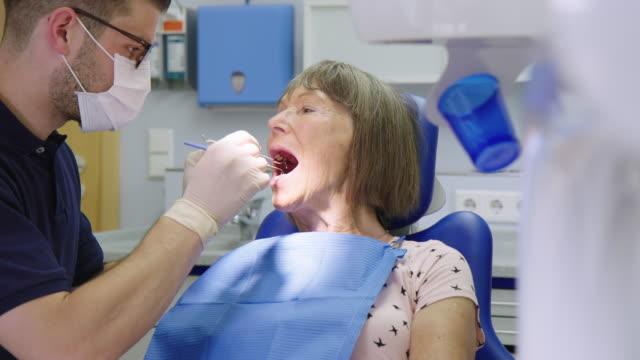 tandläkare med medicinsk utrustning som undersöker patientens - two dentists talking bildbanksvideor och videomaterial från bakom kulisserna
