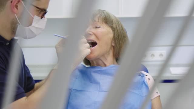 tandläkare med medicinsk utrustning som undersöker kvinnan - two dentists talking bildbanksvideor och videomaterial från bakom kulisserna