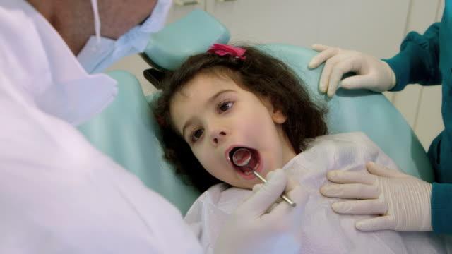 Dentista trabajando con asistente, Control dientes de jóvenes niña bebé - vídeo