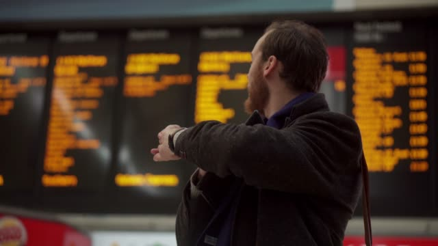 Departure board A good looking young man with a beard looks up at a departure board, checks the time and walks off with a smile. checking the time stock videos & royalty-free footage