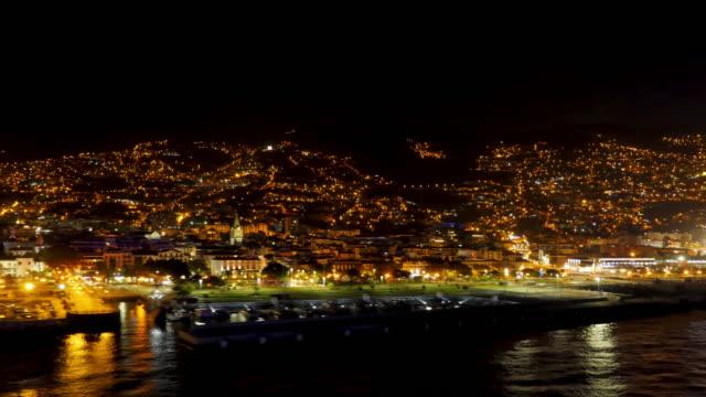 vídeos de stock e filmes b-roll de departure of a cruise ship with a view of funchal, madeira at night - funchal madeira