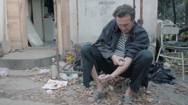 stockvideo's en b-roll-footage met een afhankelijke drugsverslaafde maakt gebruik van heroïne. buiten. 4k - amfetamine