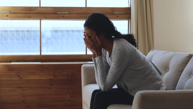 Depressed african woman feeling upset sit on sofa at home Depressed worried young african american woman in trouble feeling upset frustrated anxious regret abortion thinking of psychological problem suffer from anxiety concept sit on sofa at home alone mental wellbeing stock videos & royalty-free footage