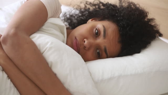 Depressed african woman lying on bed embraces pillow feels unhappy Close up depressed mixed race young woman lying on bed at home embraces pillow feels unhappy and lonely, black cheated girl suffers hurt from break up with boyfriend, unwanted pregnancy, pms concept anxiety stock videos & royalty-free footage
