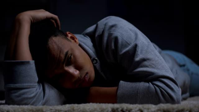 depressiver afroamerikanischer teenager leidet unter einsamkeit im dunklen raum, missbrauch - depression stock-videos und b-roll-filmmaterial