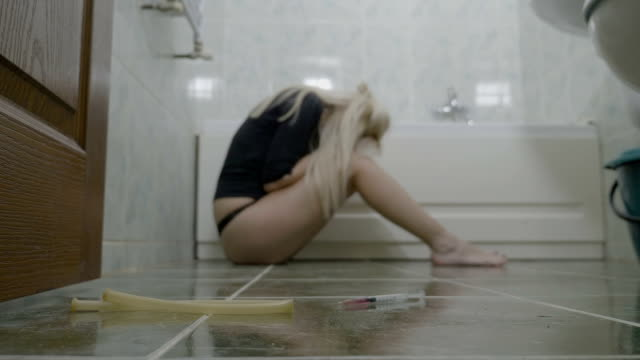 Depressed attractive woman sitting on the bathroom floor and thinking about her problems with regret after a heroin shot in her veins video