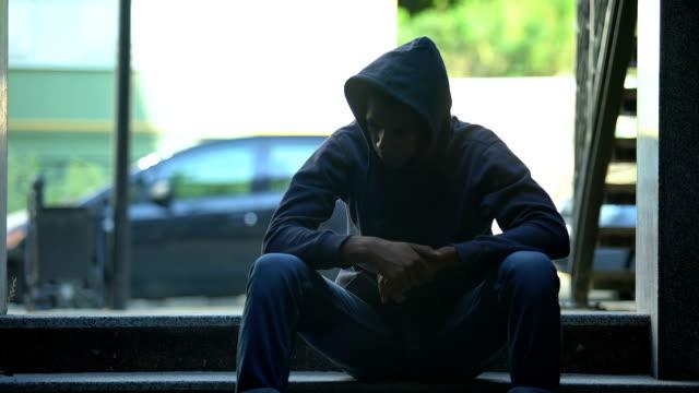 vidéos et rushes de garçon noir déprimé s'asseyant sur des escaliers contemplant au sujet de la vie dure dans le ghetto - culture des jeunes
