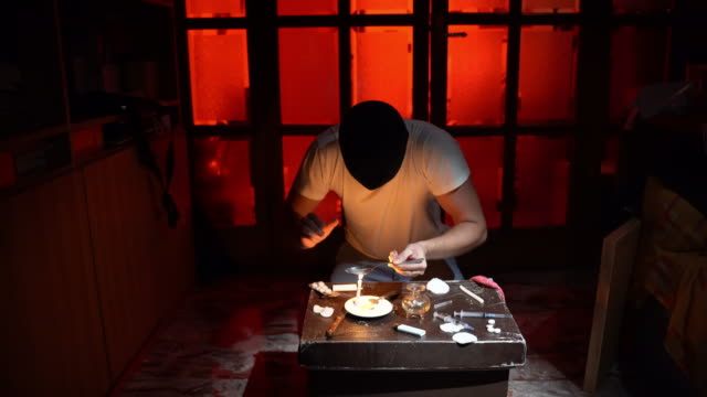 Depressed drug dealer with shaking hands preparing illegal packs of heroin in underground lab. Paraphernalia, cocaine and heroin on the table. Drug hell with blinking red light and narcotic abuse. Dose sorting and criminal business