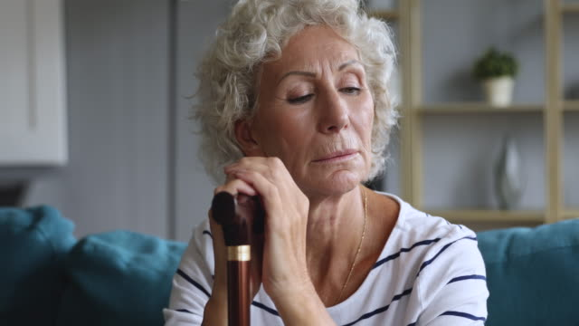 Depressed elderly woman holding walking cane stick sit on sofa Depressed thoughtful elderly adult woman holding walking cane stick sit alone on sofa, pensive sad old senior grandma feeling lonely suffer from geriatric health problems concept, close up view orthopedic equipment stock videos & royalty-free footage