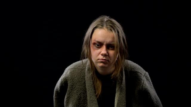 vídeos y material grabado en eventos de stock de deprimida mujer rehén con moretones en la cara mirando a cámara, víctima de la guerra - human trafficking
