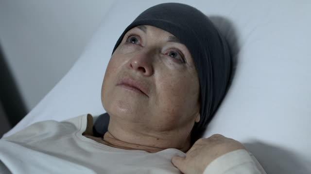 vídeos y material grabado en eventos de stock de mujer deprimida en bufanda acostada en la cama sin esperanza de recuperación, tratamiento oncológico - geriatría