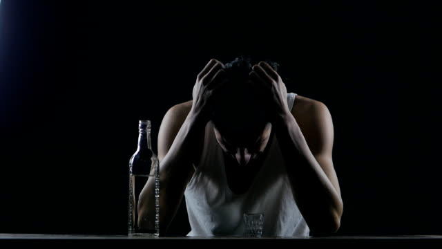 depressed man crying with a bottle of vodka. man in despair video