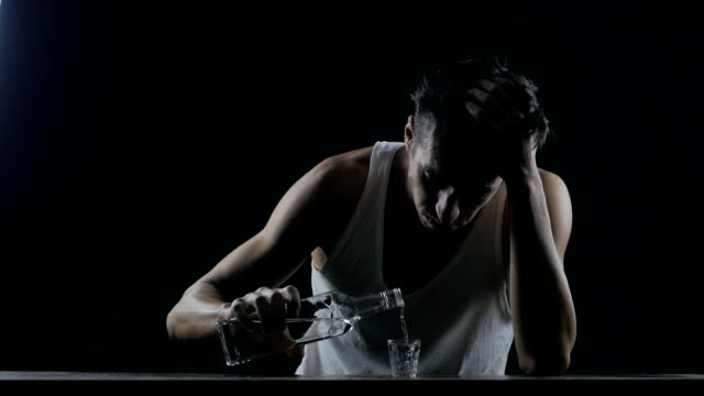 depressed man drinking alcohol alone in a dark room. man in despair video