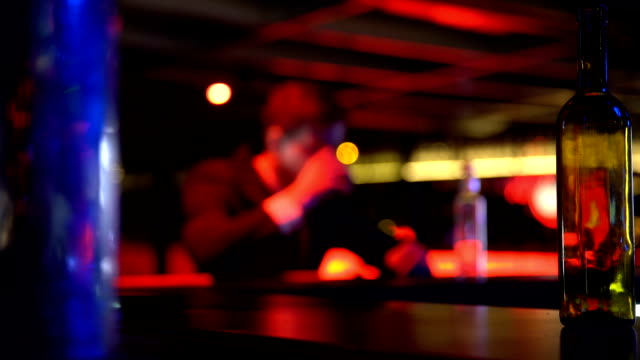 Depressed man drinking whiskey alone in nightclub, thinking over problems video