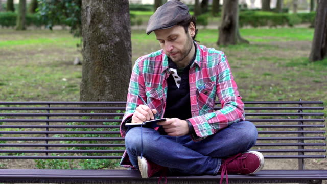 depressed man on a bench at the park writes her thoughts in a diary video