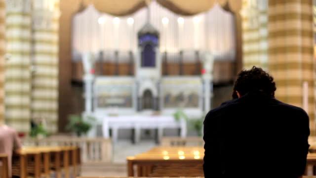 depressed man praying in a church video