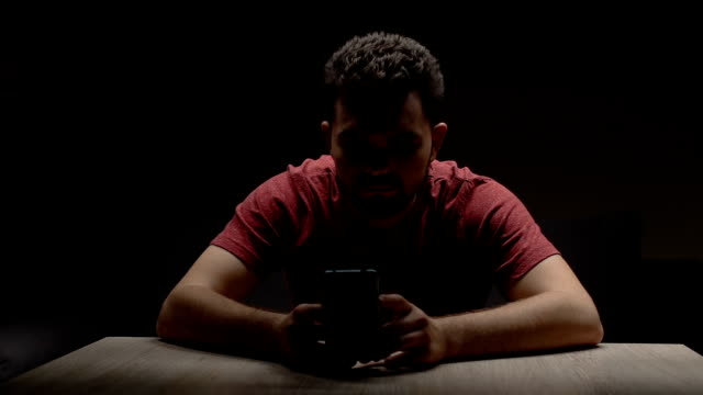 Depressed man sitting in dark empty room with smartphone, waiting for call video