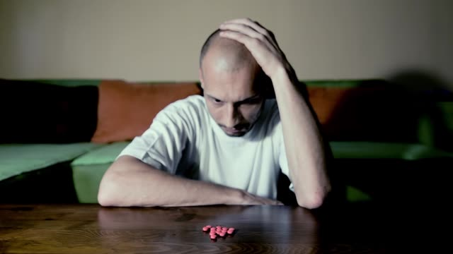 depressed man suffering from suicidal depression want to commit suicide by taking strong medicament drugs and pills pain killers while he sitting in his dark room selective focus moody dramatic look - assuefazione video stock e b–roll