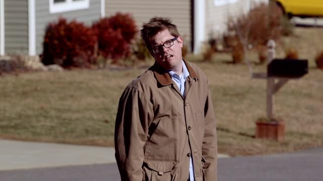 A depressed man walks away in suburbia video