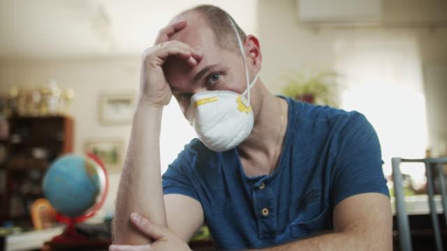 stockvideo's en b-roll-footage met gedeprimeerde mens die antivirusmasker draagt dat thuis blijft - ongerustheid