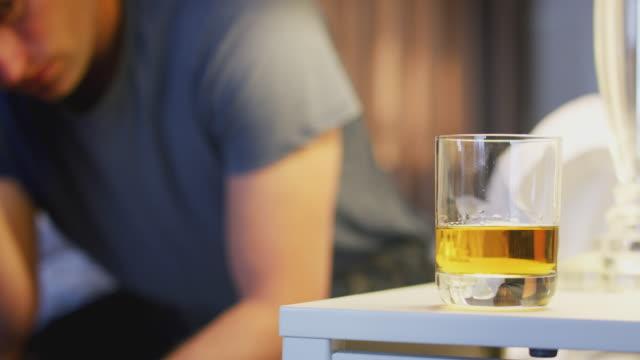 vídeos de stock, filmes e b-roll de pijamas desgastando do homem deprimido que sentam-se no lado da cama com vidro do uísque no armário da cabeceira - bebida alcoólica