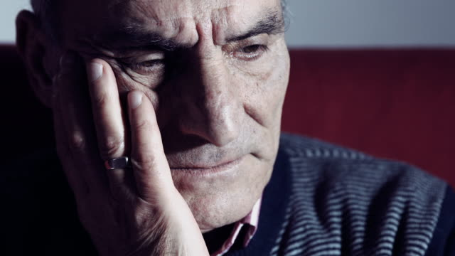 depressed old man sitting alone on the sofa: sadness, pensive, thougthful video