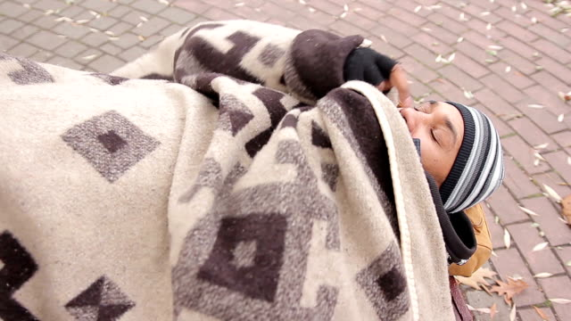 Depressed poor man lying on cold bench outdoors covered with shabby blanket video