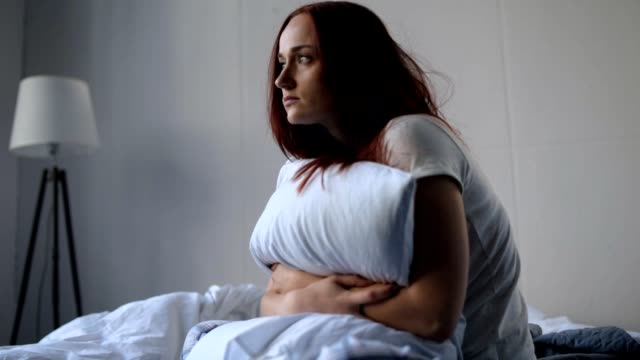 Depressed sad woman sitting in her bedroom End of my life. Distressed adult woman embracing her pillow and feeling sad while sitting in her bedroom exhaustion stock videos & royalty-free footage