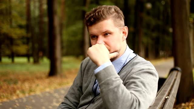 Depressed, sad young businessman sitting in the park video