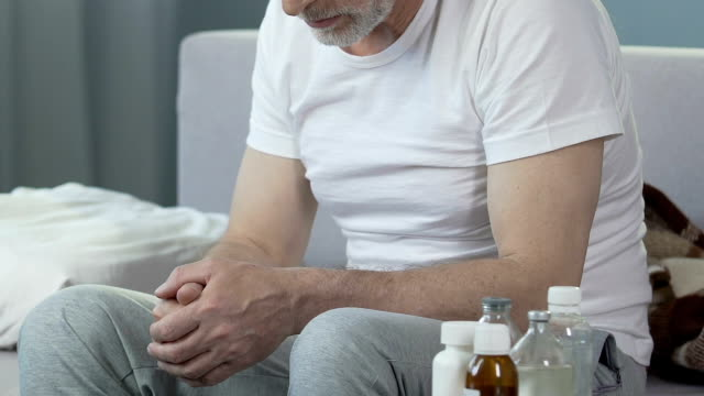 Depressed senior male sitting on bed, bottles with medicines standing nearby video