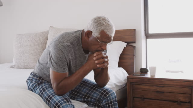 Depressed Senior Man Looking Unhappy Sitting On Side Of Bed At Home
