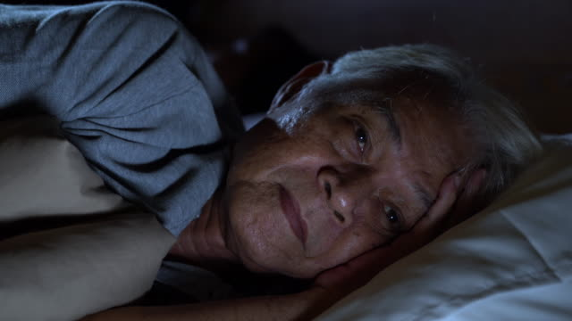 Video A depressed senior man lying in bed cannot sleep from insomnia