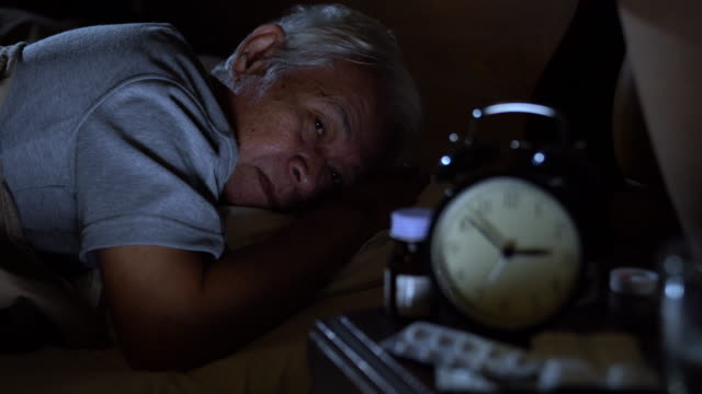 A depressed senior man lying in bed cannot sleep from insomnia A depressed senior man lying in bed cannot sleep from insomnia insomnia stock videos & royalty-free footage