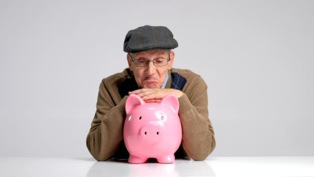 Depressed senior with a piggybank gesturing with his hands video