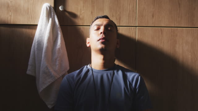 Depressed soccer player looking at camera in the locker room