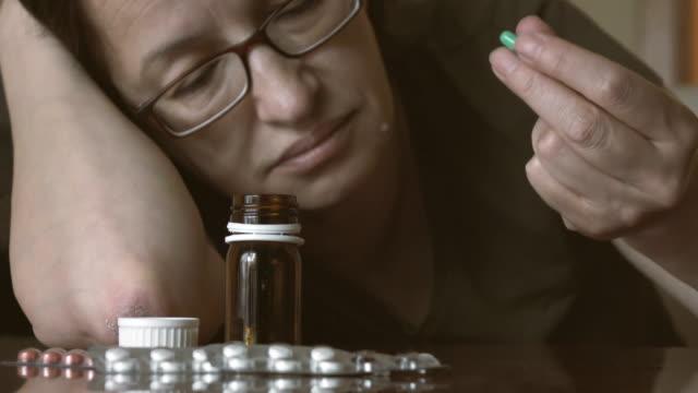 deprimerad kvinna bredvid en hel del piller - missbruk koncept bildbanksvideor och videomaterial från bakom kulisserna