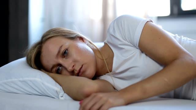 depressive frau aufgestützt auf kissen im bett - depression stock-videos und b-roll-filmmaterial