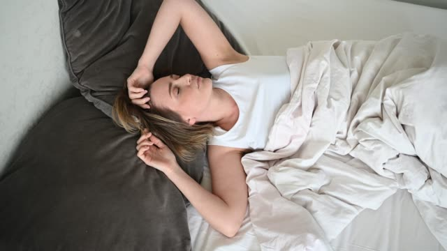 depressed woman tormented by restless sleep, she is exhausted and suffering from insomnia, bad dreams or nightmares, psychological problems. inconvenient uncomfortable bed or mattress. - {{relatedsearchurl(carousel.phrase)}} video stock e b–roll