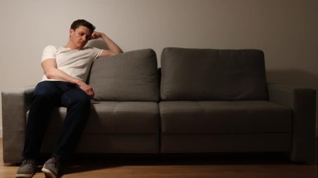 밤에 회색 소파에 우울된 젊은 성인 남자 - 앉음 스톡 비디오 및 b-롤 화면