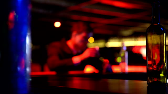 Depressed young man drinking alcohol alone in bar, failure, problems in life video