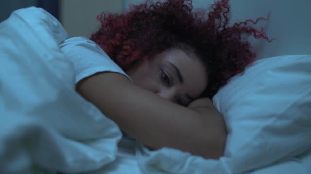 Depressed young woman lying in bed under blanket, thinking of problems, breakup Depressed young woman lying in bed under blanket, thinking of problems, breakup relationship breakup stock videos & royalty-free footage
