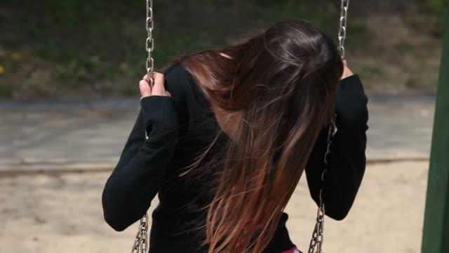 vidéos et rushes de vieillard déprimé jeune femme sur balançoire - extérieurs d écoles