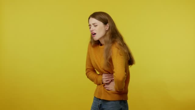 depressed young woman rubbing painful belly, frowning suffering stomach ache, menstrual cramps - голодный стоковые видео и кадры b-roll