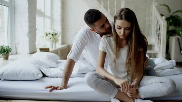 Depressed young woman sitting in bed and crying while her boylfriend come and embrace her and kiss in bedroom at home video