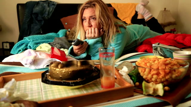 Depressive woman eating and waching tv video