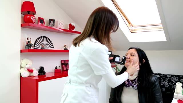 皮膚科医は、写真当と患者の皮膚を確認してください。 ビデオ