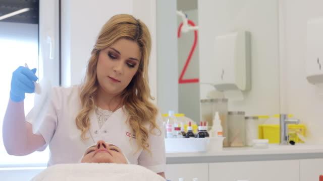 dermatologist cooling down patient's skin with a hand fan - kosmetyczka praca w salonie piękności filmów i materiałów b-roll