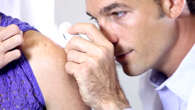 Dermatologist examining a patient A male dermatologist closely examining the skin on the shoulder of a female patient. dermatology stock videos & royalty-free footage