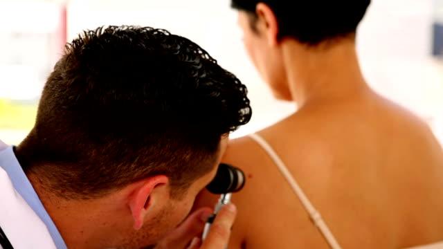 Examinar un dermatólogo womans back y sonriendo a la cámara - vídeo