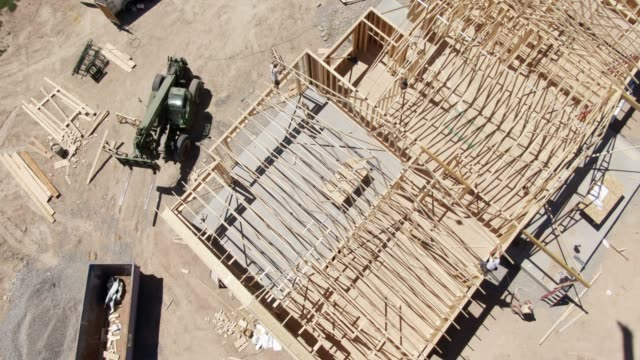 Descending Aerial Drone Shot of a Group of Construction Workers Framing a House on a Sunny Day